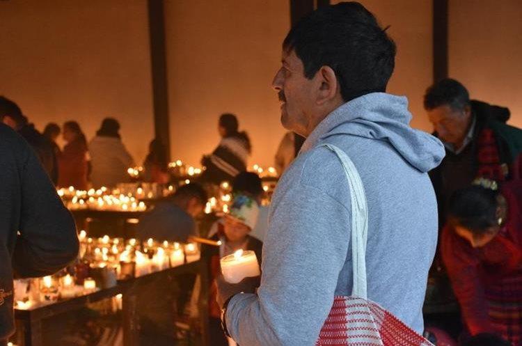 Un peregrino con una vela en mano realiza una petición a la milagrosa imagen.(Foto Prensa Libre: Mario Morales)