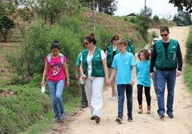Sandra camina hacia el colegio acompañada de Mónica Vicente y su familia. Foto Prensa Libre: