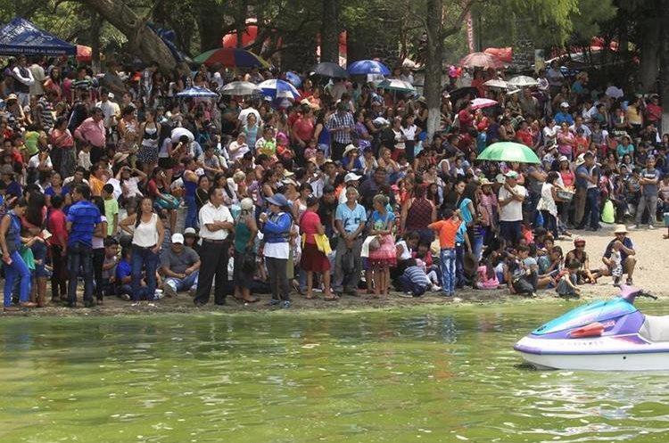 Fieles esperan a la orilla del lago, el recorrido de la procesión del Niño Dios. (Foto Prensa Libre: Carlos Hernández).