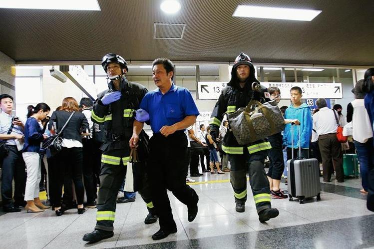 Un pasajero es escoltado por los bomberos después de salir de un tren bala en Odawara,Japón. (Fot Prensa Libre:AP).