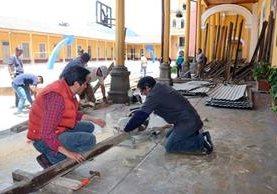 Padres de familia, estudiantes y maestros trabajan en la elaboración de estructuras de madera para el muro que circulará el área restringida en el Invo, en Xela. (Foto Prensa Libre: Carlos Ventura)