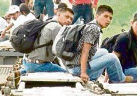 Unos migrantes cruzan un tramo peligroso en México sobre un tren.