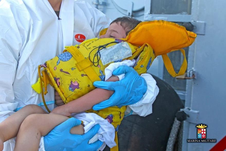 Personal de la Marina italiana asisten a un menor que fue rescatado del mar Mediterráneo. (Foto Prensa Libre: AFP).