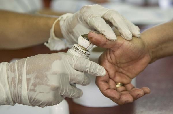 La junta receptora de votos pinta con tinta el dedo de un ciudadano después de votar. (EFE).