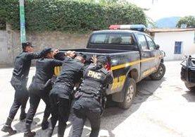 Un grupo de agentes empuja un autopatrulla en mal estado, lo que ocurre con frecuencia en distintas comisarías del país. (Foto Prensa Libre: Ángel Julajuj)
