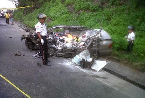 Bomberos observan el vehículo en el que se desplazaban las dos víctimas mortales. (Foto Prensa Libre: Enrique Paredes)