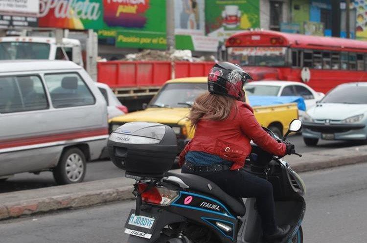 Una mujer conduce motocicleta sobre la calzada San Juan. (Foto Prensa Libre: Estuardo Paredes)
