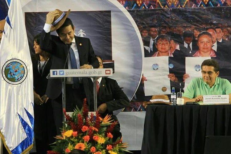 El presidente Jimmy Morales, se coloca un sombrero durante una actividad del magisterio, donde lo acompaña el dirigente del Steg, Joviel Acevedo. (Foto Prensa Libre: Esbin García)