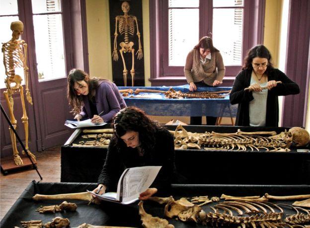 Miembros del equipo del EAAF revisan varios restos en el laboratorio del equipo. EAAF