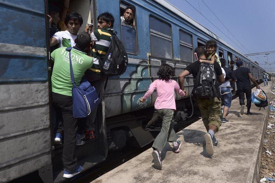 Varios inmigrantes corren para subir a bordo de un tren en dirección a la frontera con Serbia en la estación de Gevgelija en Macedonia. (Foto Prensa Libre: EFE).