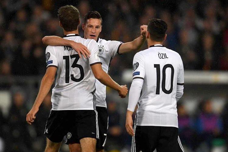 Thomas Müller (13) y Mesut Ozil (10) felicitan a Draxler, por haber marcador el primer gol de los alemanes contra Irlanda del Norte (Foto Prensa Libre: AFP)