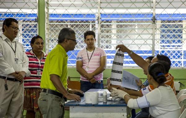 Integrantes de una junta receptora de votos muestran una boleta a un nicaragüense. (EFE).