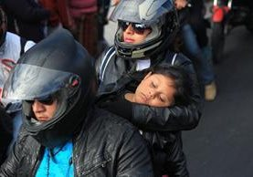 Un niño duerme en los brazos de su madre a bordo de una motocicleta; ignora que su vida corre peligro. (Foto Prensa Libre: Esbin García)