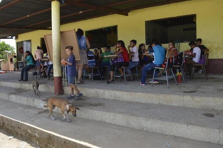 Un grupo de estudiantes de la escuela rural de Pueblo Modelo reciben clases en el pasillo del establecimiento por la falta de infraestructura. (Foto Prensa Libre: Mario Morales)