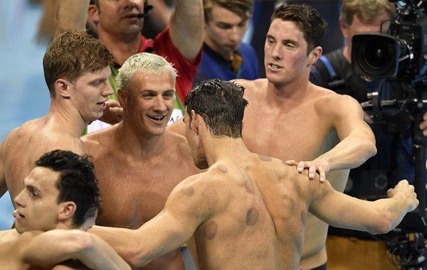 Michael Phelps (de espaldas) es felicitado por sus compañeros, después de cerrar de gran manera la prueba de natación de 4X200 metros (Foto Prensa Libre: AP)