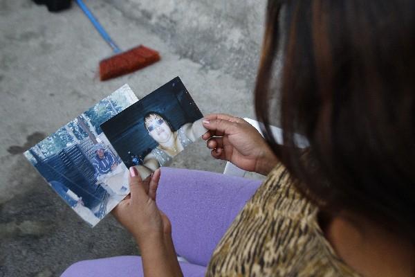 una familiar observa las fotos  de los padres de los hermanos Rosales Hernández.