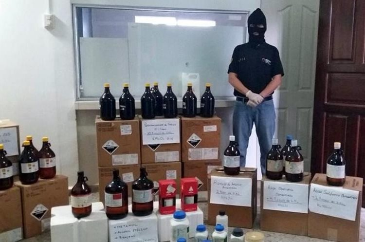 "Handout photo released by the Honduran Criminal Investigation Technical Agency (ATIC) of an ATIC member standing guard next to chemical substances seized to the Salvatrucha gang in the Avalanche operation in San Pedro Sula, 240 km of Tegucigalpa on February 23, 2016. Honduran authorities looking for new ways to combat gangs terrorizing the country are waging an operation called ""Avalanche"" to seize bank accounts, properties and even a small hospital from wealthy crime bosses. The police operation, which began February 23, is continuing with no defined end date.  AFP PHOTO / HONDURAN CRIMINAL INVESTIGATION TECHNICAL AGENCY"