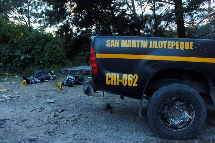 Agentes de la PNC trasladan cadáveres de dos hombres, en San Martín Jilotepeque, Chimaltenango. (Foto Prensa Libre: Víctor Chamalé)