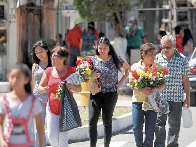un grupo  de personas lleva flores a la tumba de su difuntos, en el Cementerio General.
