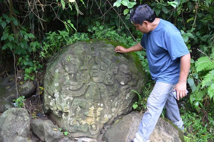 Arqueólogo muestra figuras de personajes talladas en una piedra por antepasados, la cual se halla en el sitio arqueológico de San Felipe, Retalhuleu. (Foto Prensa Libre: Jorge Tizol)