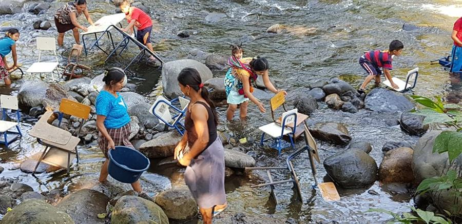 Estudiantes, maestros y padres de familia de la Escuela Rural Mixta La Fortuna de Río Bravo Suchitepéquez, lavan sus escritorios en el río Moca. (Foto Prensa Libre: Cristian Soto)