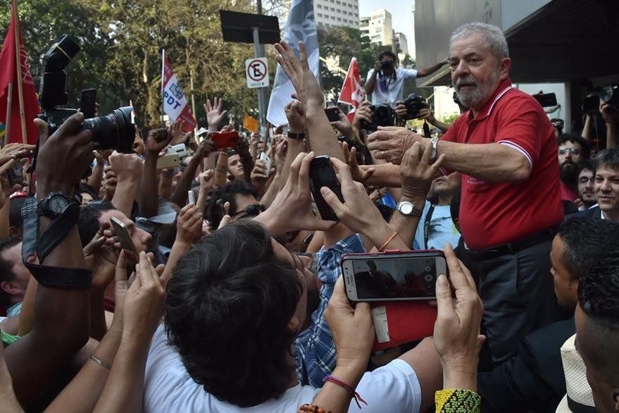 Lula da Silva saluda a simpatizantes en las afueras del hotel de Sao Paolo donde se pronunció por las acusaciones de la Fiscalía brasileña. (Foto Prensa Libre: AFP).