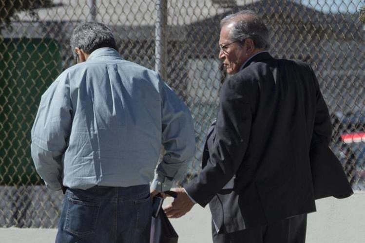 Los abogados José Luis González Meza (izquierda) y Juan Pablo Badillo (derecha), caminan en las afueras del penal del Altiplano. (Foto Prensa Libre: AFP).