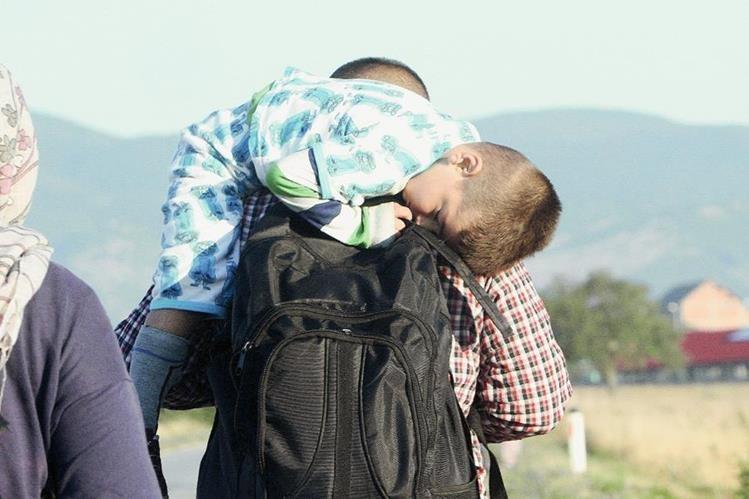 Un niño sirio huye del conflicto junto a su padre en la localidad de Presevo, Serbia. (Foto Prensa Libre: EFE)