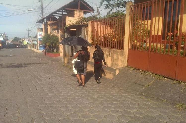Algunos vecinos tuvieron que usar sombrilla para evitar que les cayera ceniza. (Foto Prensa Libre: Víctor Chamalé)