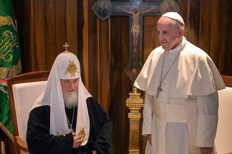 Pope Francis (R) and the head of the Russian Orthodox Church, Patriarch Kirill, are pictured during a historic meeting in Havana on February 12, 2016. Pope Francis and Russian Orthodox Patriarch Kirill kissed each other and sat down together Friday for the first meeting between their two branches of the church in nearly a thousand years. Francis, 79, in white robes and a skullcap and Kirill, 69, in black robes and a white headdress, exchanged kisses and embraced before sitting down smiling for the historic meeting at Havana airport.   AFP PHOTO / ADALBERTO ROQUE