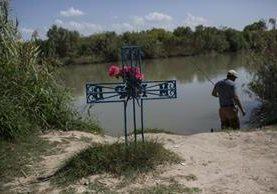un hombre pesca en el río cerca de una cruz en memoria de un migrante que murió tratando de cruzar a EE.UU. a orillas del Río Grande en Nuevo Laredo. (AP).
