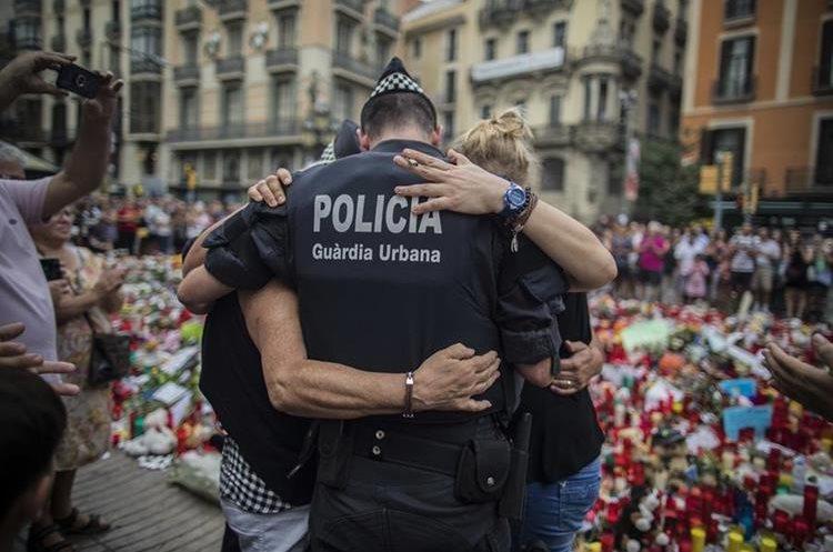 Un policía abraza a una familia a la que ayudó durante el ataque en Barcelona. (Foto Prensa Libre: AP)