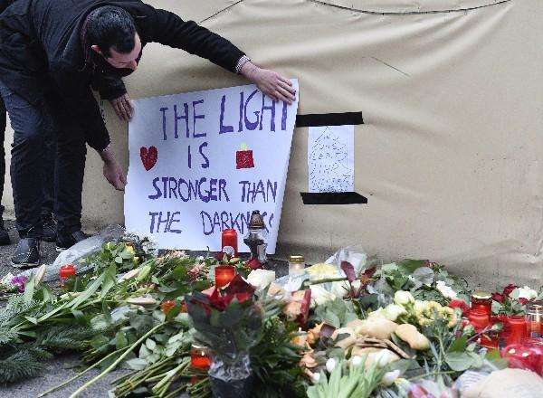 Un hombre coloca un cártel de condolencias junto a ofrendas florales en tributo a las víctimas del presunto ataque.(EFE).