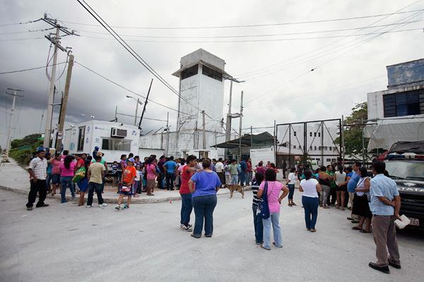 Familiares de los reos esperan noticias en las afueras del penal. (Foto Prensa Libre: del sitio noticaribe.com.mx)