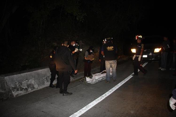 Investigadores inspecciones el cadáver localizado en la ruta a Antigua Guatemala, Sacatepéquez. (Foto Prensa Libre: Renato Melgar).