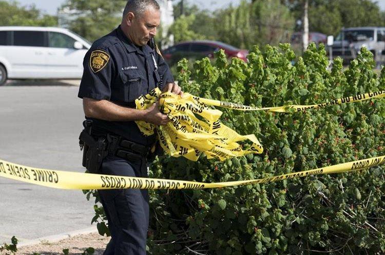 Un oficial levanta el acordonamiento de la escena del crimen luego de las investigaciones para determinar las responsabilidades del crimen. (Foto Prensa Libre: EFE)