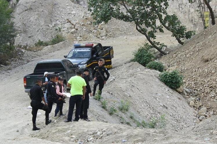 Agentes policiales observan el cadáver del hombre que fue localizado en una hondonada, en el kilómetro 67.7 de la ruta al Atlántico. (Foto Prensa Libre: Héctor Contreras)