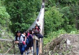 Pobladores de Sololá cruzan por un puente colgante después del deslizamiento en el cerro Lec. (Foto Prensa Libre: Conred)