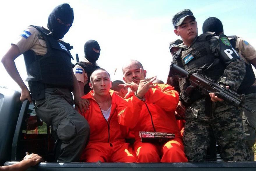 Dos líderes de la Mara 18 hacen señales hacia las cámaras durante su traslado al a prisión de máxima seguridad. (Foto Prensa Libre: AFP).