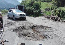 Los agujeros dificultan transitar en la carretera que rodea cinco municipios de la cuenca del Lago de Atitlán, Sololá,. (Foto Prensa Libre: Ángel Julajuj)