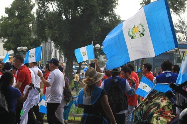 Las personas compran banderas para llevarlas junto a la antorcha encendida.
