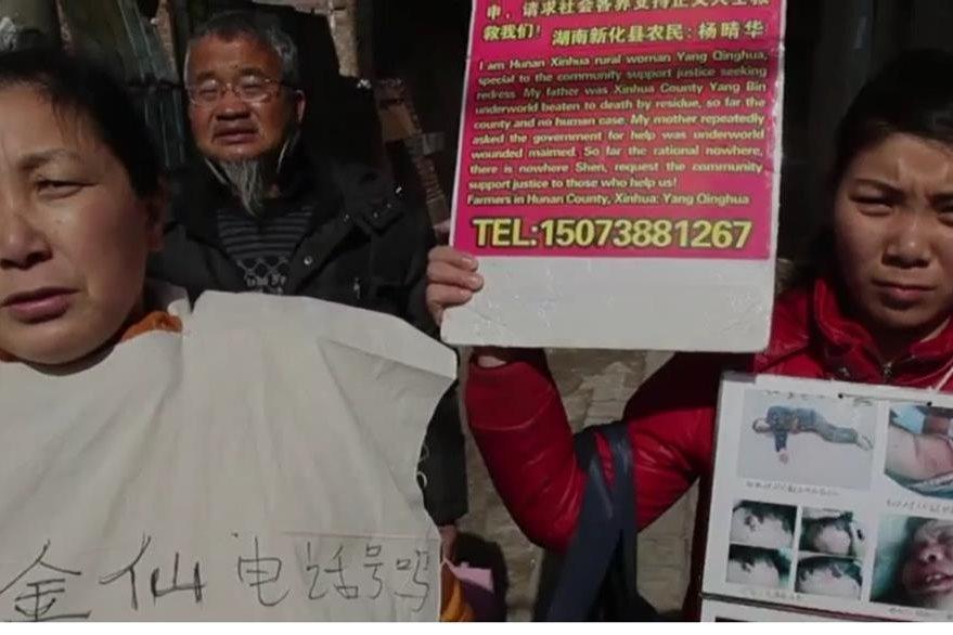 Yang Linghua muestra fotos de su padre quefue golpeado por una disputa de tierras.