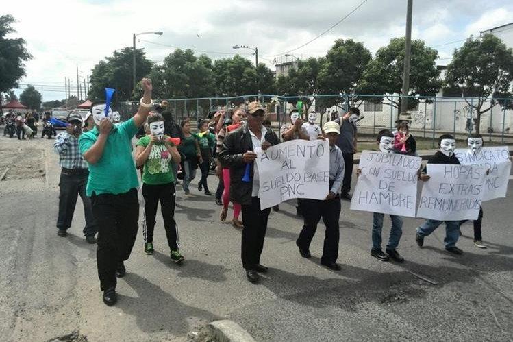 Policías, ex agentes de la PNC y familiares participan en una marcha en donde exijen mejores condiciones laborales. (Fot Prensa Libre: Foto Esbin García)