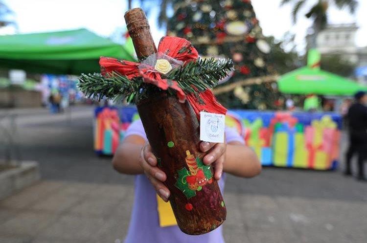 Una interna muestra una botella que hizo para venderla en el bazar denominado Sueños y Oportunidades. (Foto Prensa Libre: Carlos Hernández).