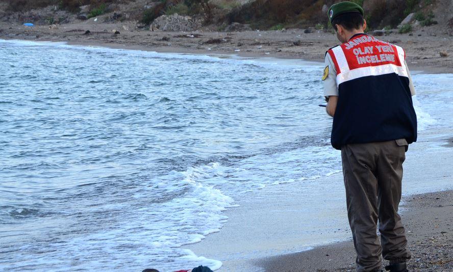 El policía turco, al momento en que descubrió el cuerpo del infante inerte en la playa de Bodrum. (Foto Prensa Libre: EFE).