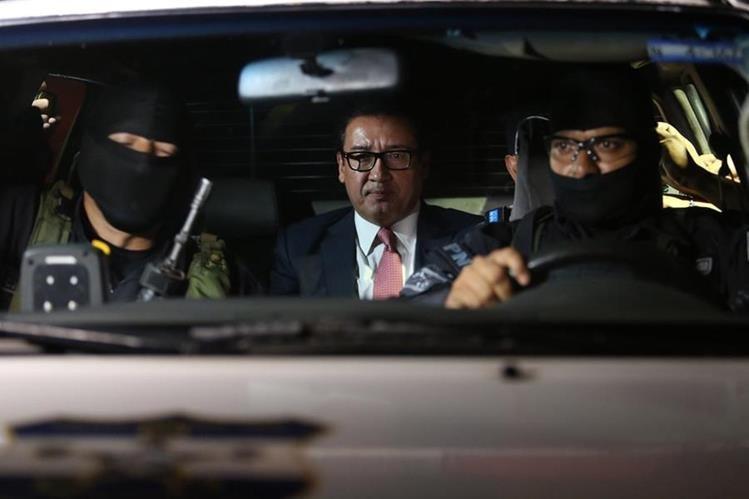 Agentes de la Policía Nacional Civil trasladan al exfical salvadoreño, Luis Martínez. (Foto Prensa Libre: EFE).
