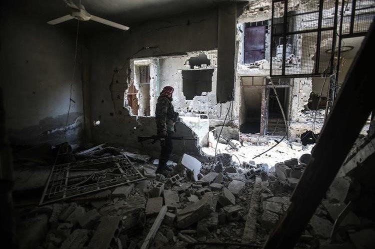Un rebelde observa los escombros de ataques armados ocurrido en el asediado vecindario de Teshreen, Damasco.