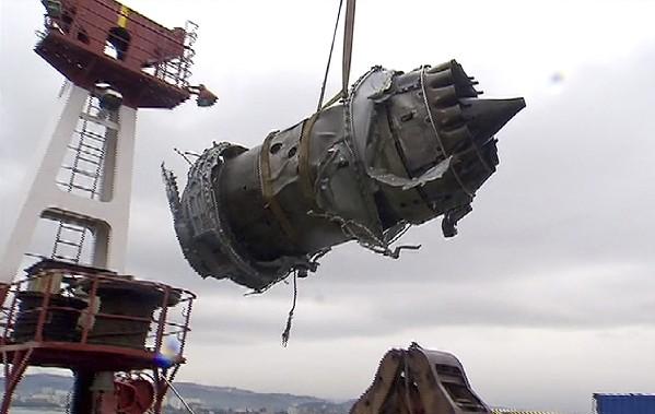 Un fragmento de un motor de avión levantado por buzos en un barco.(AFP).