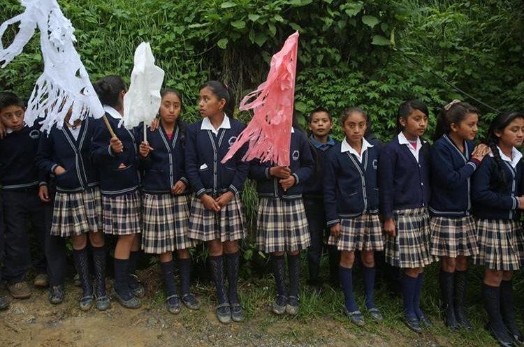 Estudiantes hacen un pasillo afuera de la casa de sus compañeras fallecidas en el deslave. (Foto Prensa Libre: EFE)