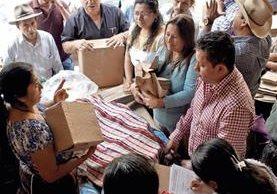 Mauricio Méndez, alcalde de San Pedro La Laguna —con camisa roja a cuadros—, supervisa entrega de bolsas de papel a comerciantes del mercado. (Foto Prensa Libre: Ángel Julajuj)